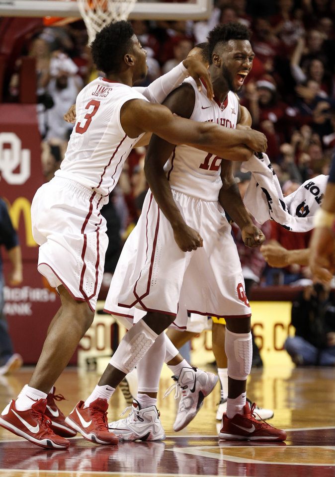 Photo - Oklahoma's Khadeem Lattin (12) gets the adulation of the team and Christian James (3) after a last second tip in for the win as the University of Oklahoma Sooner (OU) men defeat the West Virginia Mountaineers (WV) 70-68 in NCAA, college basketball at The Lloyd Noble Center on Jan. 16, 2016 in Norman, Okla. Photo by Steve Sisney, The Oklahoman
