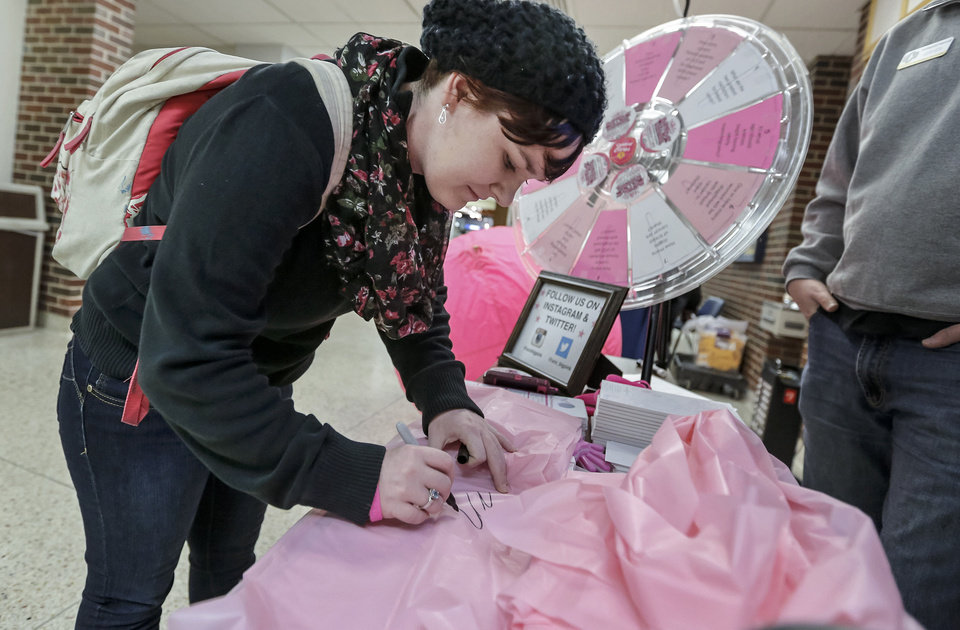 "Photo - Amanda Miller signs a pink ribbon during the University of Central Oklahoma ""Paint the Campus Pink"" week in recognition of breast cancer awareness.  PHOTO BY CHRIS LANDSBERGER, THE OKLAHOMAN"