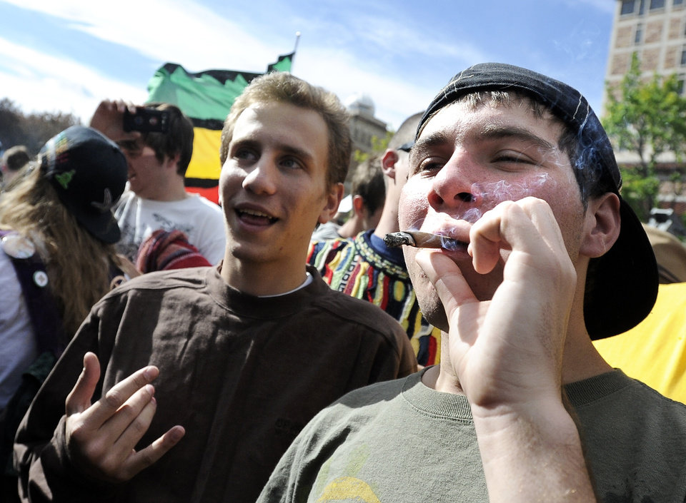 Photo -   An unidentified man smokes a blunt of marijuana outside the Duane Physics building during the 4/20 rally on the University of Colorado campus in Boulder, Colo., on Friday, April 20, 2012. Many students at the University of Colorado and other campuses across the country have long observed 4/20. The counterculture observation is shared by marijuana users from San Francisco's Golden Gate Park to New York's Greenwich Village. (AP Photo/The Daily Camera, Jeremy Papasso)