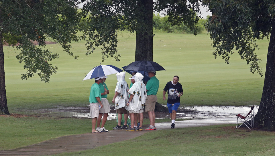 Photo - Volunteers gather under a small grove of trees that line the ninth fairway as they wait for the worst of the rain and lightening to pass after play was suspended due to inclement weather in the first round of the Sanderson Farms Championship golf tournament, Thursday, July 18, 2013 in Madison, Miss. (AP Photo/Rogelio V. Solis)