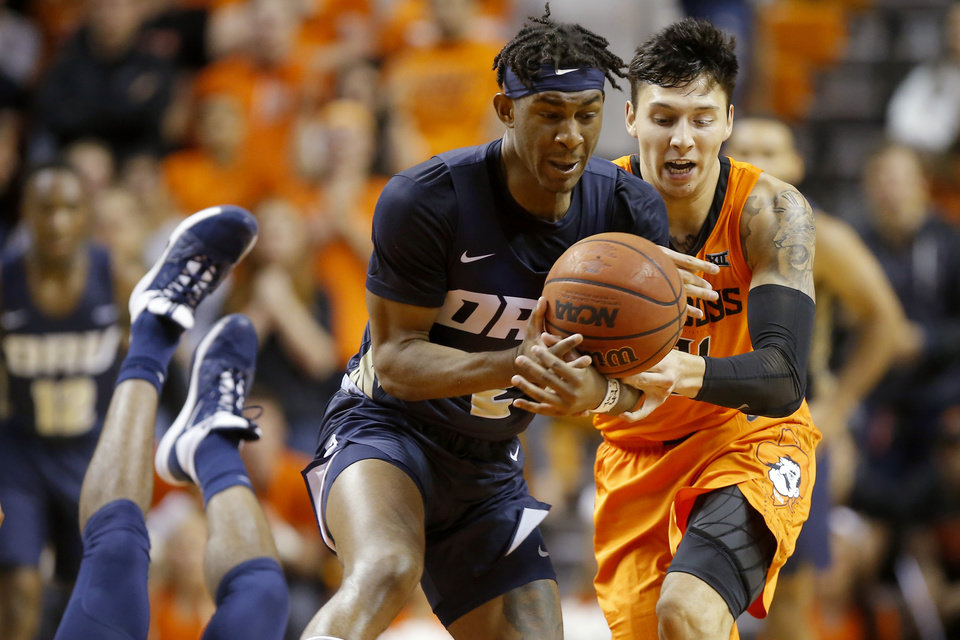 Photo - Deondre Burns of Oral Roberts grabs the ball beside Oklahoma State's Lindy Waters III (21) during an NCAA basketball game between the Oklahoma State University Cowboys (OSU) and the Oral Roberts Golden Eagles (ORU) at Gallagher-Iba Arena in Stillwater, Okla., Wednesday, Nov. 6, 2019. Oklahoma State won 80-75. [Bryan Terry/The Oklahoman]