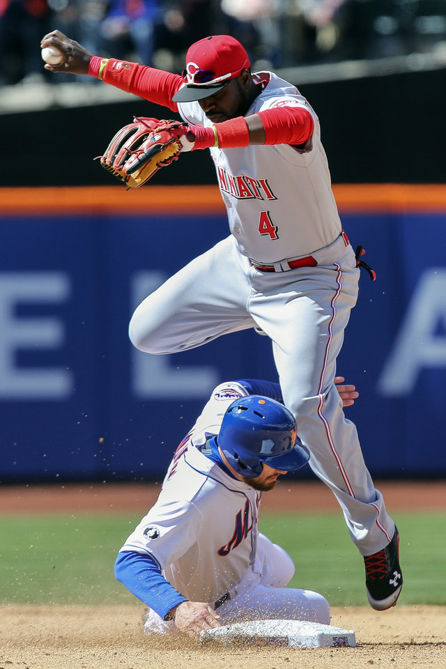 Photo - Cincinnati Reds second baseman Brandon Phillips (4) leaps over New York Mets' Daniel Murphy after making the out in the sixth inning of a baseball game at Citi Field, Saturday, April 5, 2014, in New York. (AP Photo/John Minchillo)