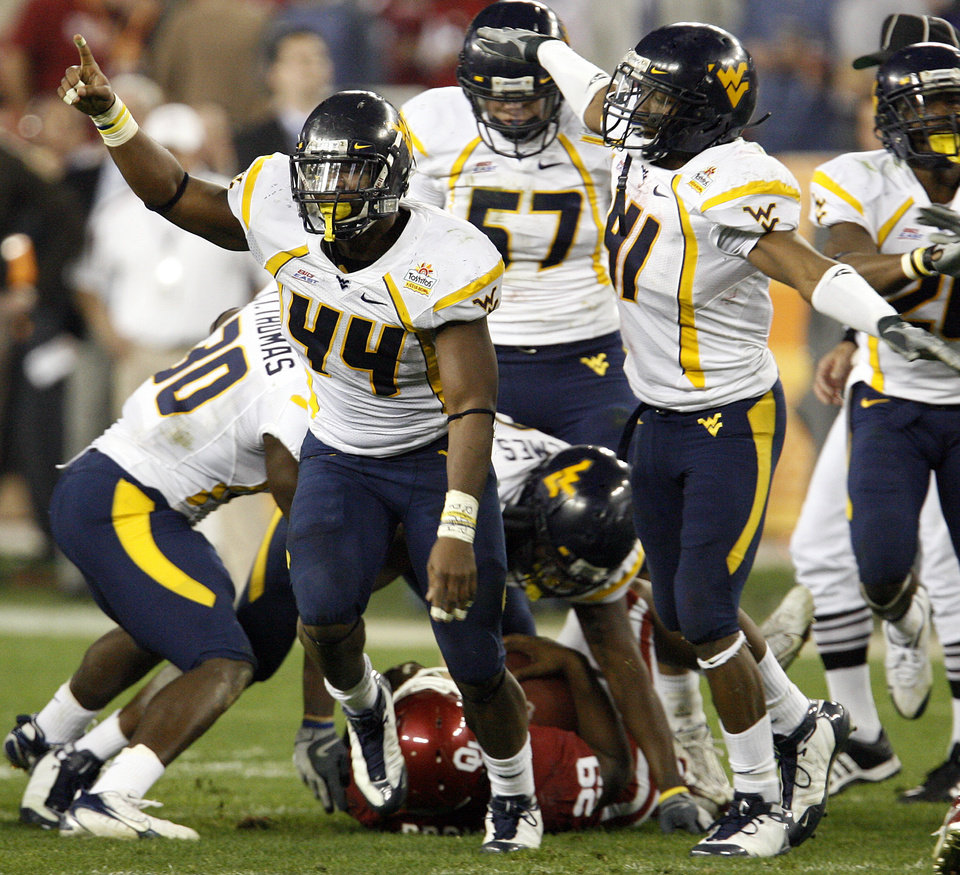Photo - West Virginia's Mortty Ivy (44) and Eric Wicks (41) react after a stop on Oklahoma's Chris Brown (29) during the first half of the Fiesta Bowl college football game between the University of Oklahoma Sooners (OU) and the West Virginia University Mountaineers (WVU) at The University of Phoenix Stadium on Wednesday, Jan. 2, 2008, in Glendale, Ariz. 
