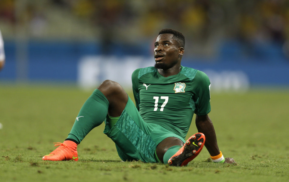 Photo - Ivory Coast's Serge Aurier sits on the ground after losing 1-2 in the group C World Cup soccer match between Greece and Ivory Coast at the Arena Castelao in Fortaleza, Brazil, Tuesday, June 24, 2014. (AP Photo/Natacha Pisarenko)