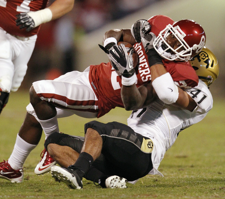 Photo - Roy Finch (22) is brought down by Terrel Smith (41) during the first half of the college football game between the University of Oklahoma (OU) Sooners and the University of Colorado Buffaloes at Gaylord Family-Oklahoma Memorial Stadium in Norman, Okla., Saturday, October 30, 2010.  Photo by Steve Sisney, The Oklahoman