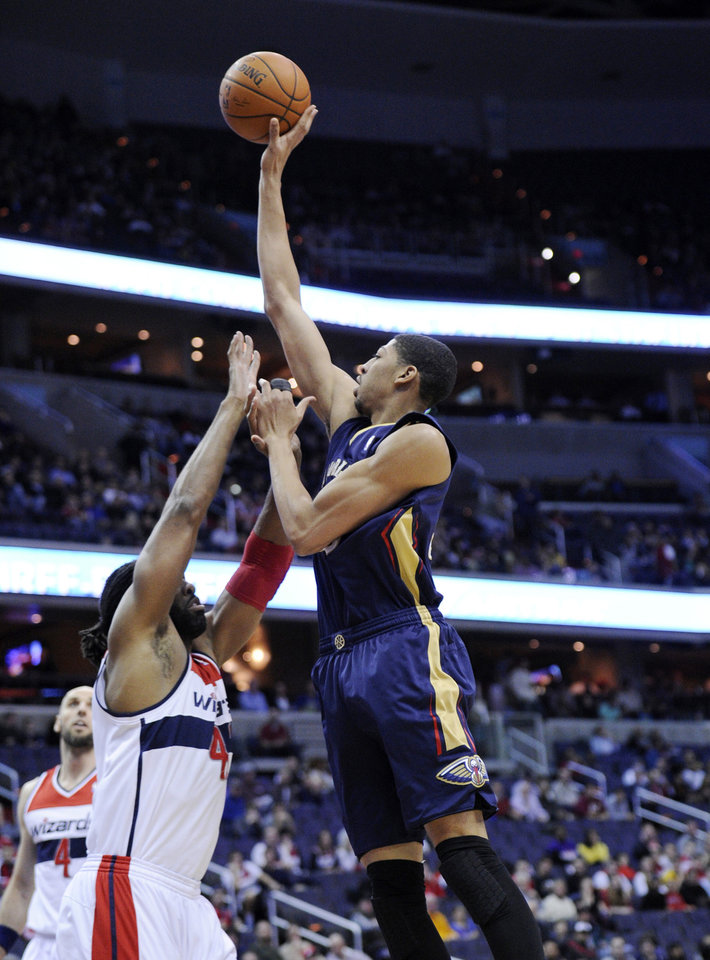 Photo - New Orleans Pelicans forward Anthony Davis, right, goes to the basket against Washington Wizards forward Nene, left, of Brazil, during the first half of an NBA basketball game, Saturday, Feb. 22, 2014, in Washington. (AP Photo/Nick Wass)