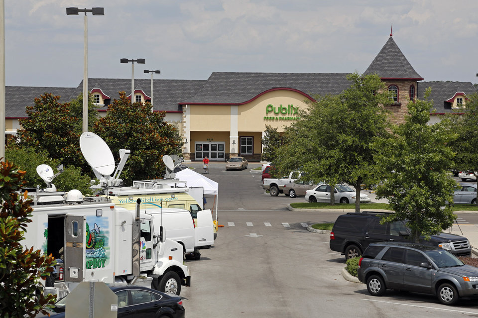 Photo - Satellite trucks line the parking lot where the highest Powerball jackpot worth an estimated $590.5 million was sold recently at this Publix supermarket located in Zephyrhills, Fla. on Sunday  May 19, 2013. (AP Photo/Scott Iskowitz)