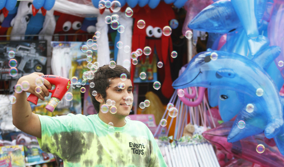Photo - George Lohman demonstrates how to use the Bubble Gun during the opening day Thursday of the Oklahoma State Fair at State Fair Park. Photo by Steve Gooch, The Oklahoman