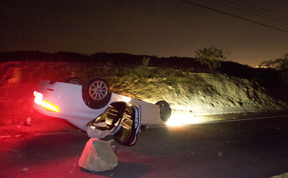 Photo - A car sits rolled over in the wake of Friday nights March 28, 2014 earthquake on Carbon Canyon Road in Brea, Calif., near Olinda Village. (AP Photo/The Orange County Register, Rod Veal)