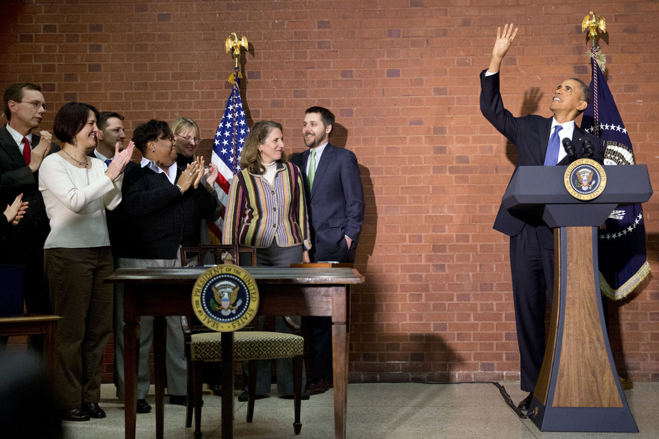 Photo - President Barack Obama waves to people in the balcony before signing the $1.1 trillion spending bill that funds the federal government through the end of September, in Washington, Friday, Jan. 17, 2014 at Jackson Place, a conference center near the White House. Obama signed the measure the day before federal funding was set to run out and was joined by aides who did much of the work negotiating it. (AP Photo/Jacquelyn Martin)