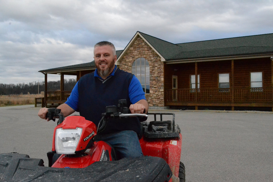 In this Nov. 21, 2013 photo, Shawn Owens, Knott County tourism director, sits on an all-terrain vehicle at the Mine Made Adventure Park in Leburn, Ky. The ATV park was built on a former coal mine and local officials hope the park can generate tourism dollars for the small Appalachian county (AP Photo/Dylan Lovan)