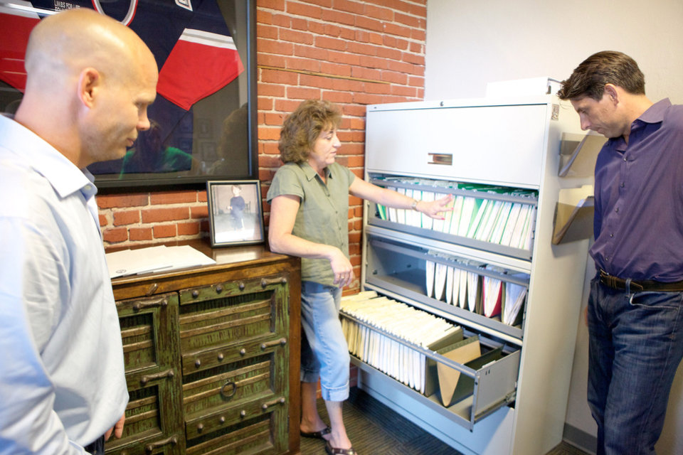 Photo - Pam Timmons, Limbs for Life Director of Development, shows the organization's filing system to Dave Mortensen (left) and Chuck Runyon during filming of ABC's