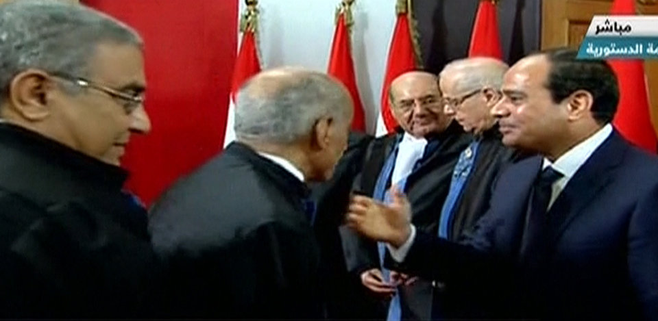 Photo - This image made from Egyptian State Television shows newly sworn in President Abdel-Fattah el-Sissi, right, with judges as he is congratulated after after a ceremony at the Supreme Constitutional Court in Cairo, Egypt, Sunday, June 8, 2014. El-Sissi's inauguration Sunday comes less than a year after the 59-year-old career infantry officer ousted the country's first freely elected president, the Islamist Mohammed Morsi, following days of mass protests by Egyptians demanding he step down. (AP Photo/Egyptian State Television)