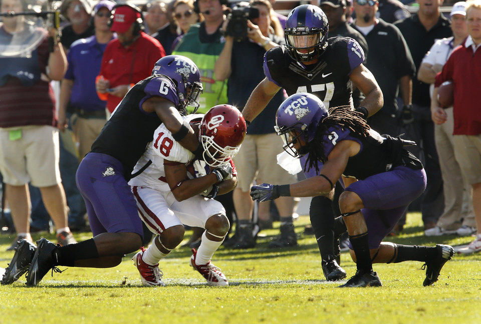 Photo - TCU's Elisha Olabode (6) and Jason Verrett (2) bring down Oklahoma's Jalen Saunders (18) after a catch during the second half of the college football game where the University of Oklahoma Sooners (OU) defeated the Texas Christian University Horned Frogs (TCU) 24-17 at Amon G. Carter Stadium in Fort Worth, Texas, on Saturday, Dec. 1, 2012. Photo by Steve Sisney, The Oklahoman