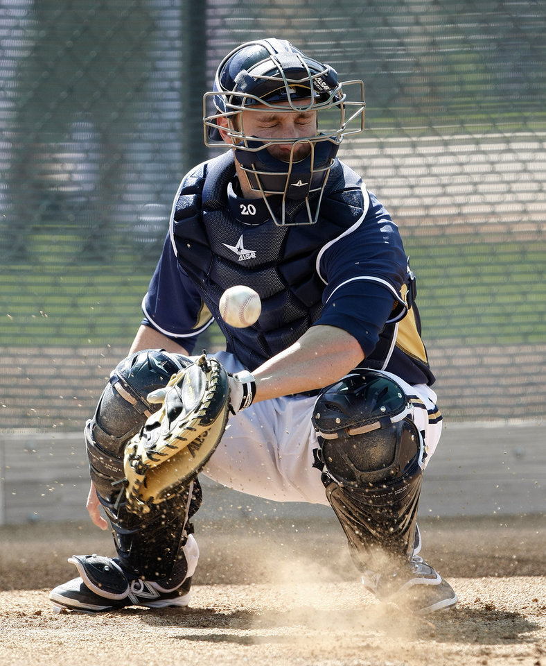 Photo - Milwaukee Brewers catcher Jonathan Lucroy (20) blocks a ball in the dirt during a spring training baseball practice, Sunday, Feb. 22, 2014, in Phoenix. (AP Photo/Rick Scuteri)