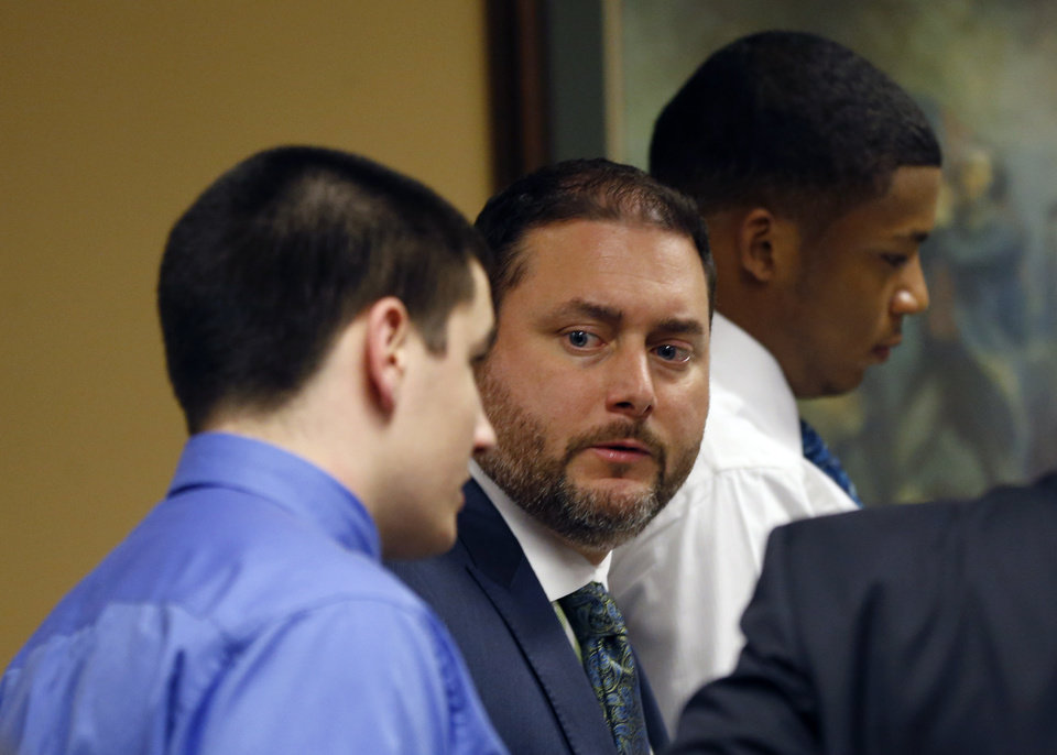 Photo - From left, defendant Trent Mays, 17, his defense attorney Adam Nemann, and co-defendant ,16-year-old Ma'lik Richmond get up to leave their trial on rape charges more than 13 hours after the start of their third day in juvenile court on Friday, March 15, 2013 in Steubenville, Ohio. Mays and Richmond are accused of raping a 16-year-old West Virginia girl in August 2012. (AP Photo/Keith Srakocic, Pool)