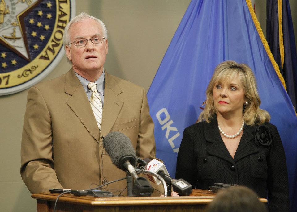Photo - Gov. Mary Fallin looks on as Brad Yarbrough, DHS commission chairman, talks about the Department of Human Service's improvements in
