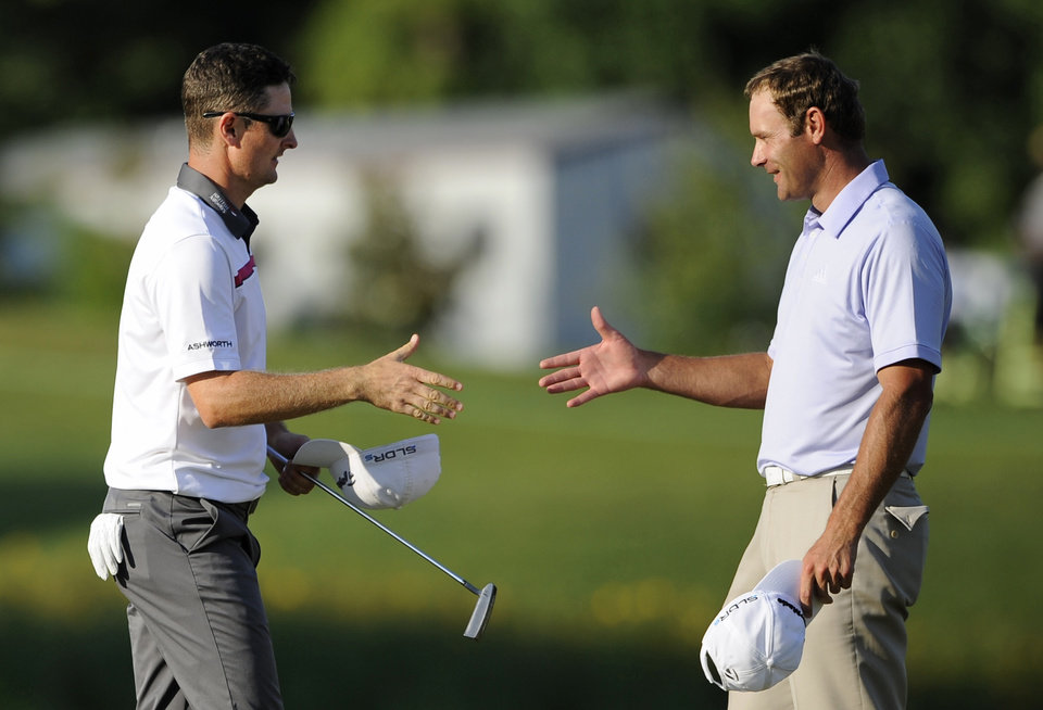 Photo - Justin Rose, left, of England, shakes hands with Shawn Stefani after Rose won the Quicken Loans National PGA golf tournament in a playoff round against Stefani, Sunday, June 29, 2014, in Bethesda, Md. (AP Photo/Nick Wass)