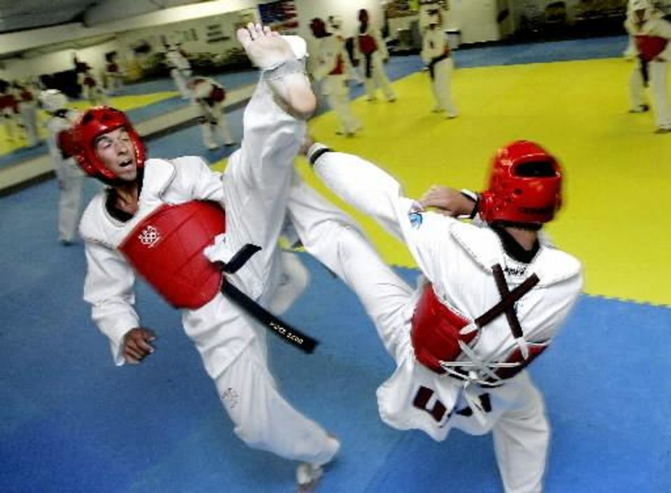 Photo - Jason  Neville, left, and Jon Perieda practice at Poos Taekwondo in Edmond, Wednesday, July 6, 2005. The two are members of the U.S. National Junior and Collegiate taekwondo team. By Bryan Terry