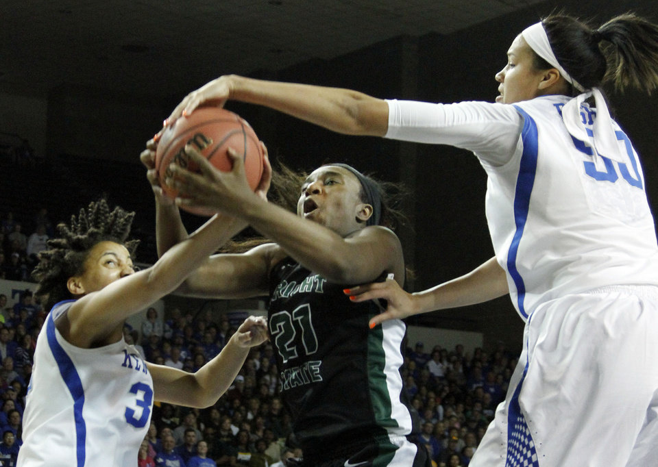Photo - Wright State's Tayler Stanton (21) shoots as Kentucky's Kastine Evans, left, and Azia Bishop defend during the first half of a first-round game in the NCAA women's college basketball tournament in Lexington, Ky., Saturday, March 22, 2014. (AP Photo/James Crisp)