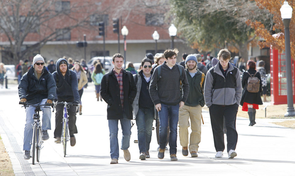Photo - University of Oklahoma students walk to class Monday on the South Oval. It was the first day of spring classes in Norman.  Photos By Steve Gooch, The Oklahoman