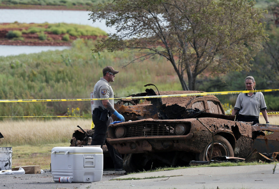Photo - Law enforcement officials from multiple agencies examine the two cars pulled from Foss Lake, in Foss, Okla., Wednesday, Sept. 18, 2013. The Oklahoma State Medical ExaminerÂ's Office says authorities have recovered skeletal remains of multiple bodies in the Oklahoma lake where the cars were recovered. (AP Photo/Sue Ogrocki) ORG XMIT: OKSO104