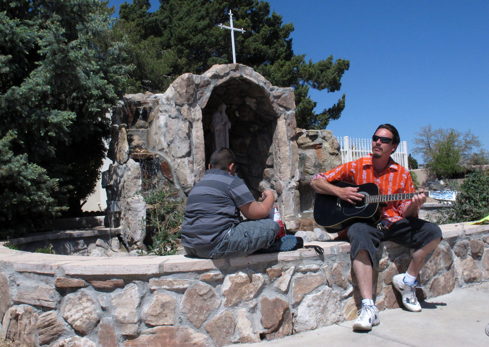 Photo - William Patterson, 34, of Pueblo, Colo., plays guitar outside the St. Jude Thaddeus Catholic Church in Albuquerque, Monday, April 29, 2013, a day after a man stabbed several churchgoers Sunday as Mass was ending. Police say four parishioners were injured, including church choir director Adam Alvarez, but none have life-threatening injuries. Lawrence Capener, 24, is charged with three counts with aggravated battery and is being held on $75,000 bail. (AP Photo/Russell Contreras)