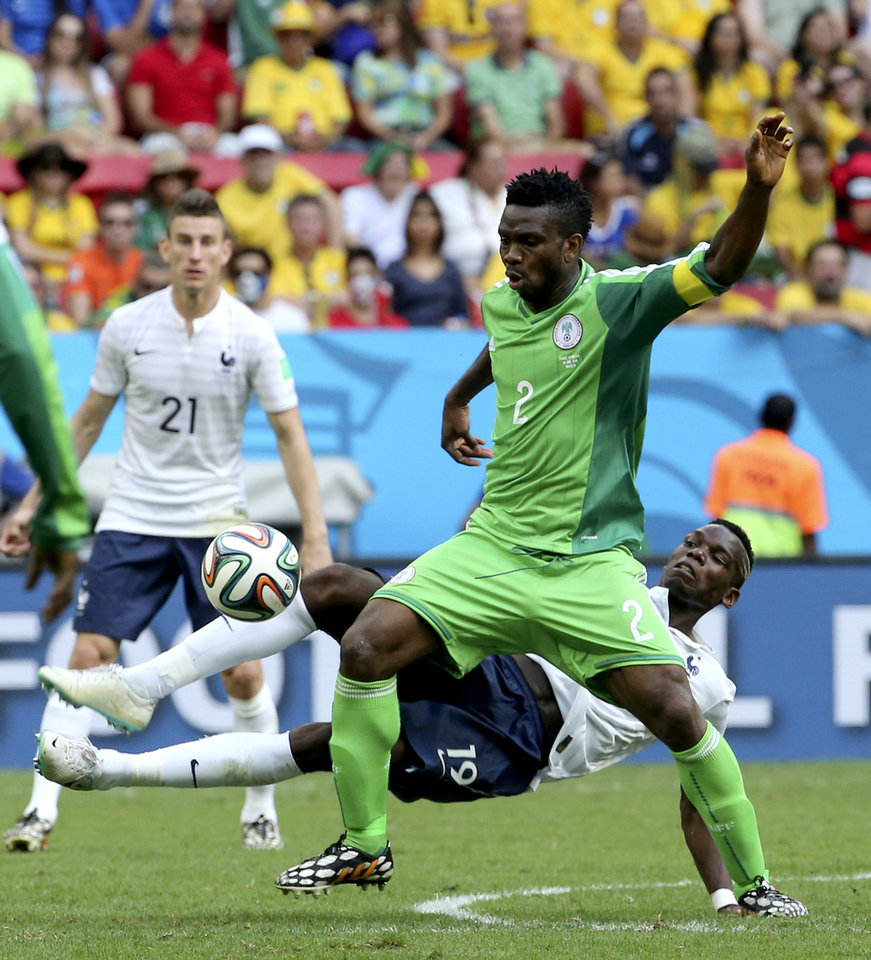 Photo - France's Paul Pogba (19) challenges Nigeria's Joseph Yobo (2) during the World Cup round of 16 soccer match between France and Nigeria at the Estadio Nacional in Brasilia, Brazil, Monday, June 30, 2014. (AP Photo/David Vincent)