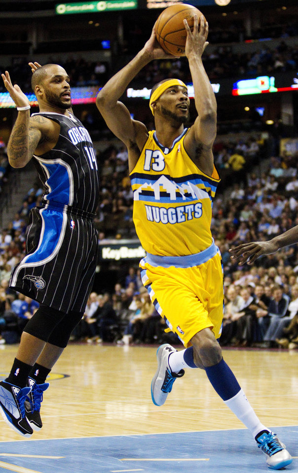 Denver Nuggets' Corey Brewer (13) drives past Orlando Magic's Jameer Nelson (14) for a layup during the first quarter of an NBA basketball game, Wednesday, Jan. 9, 2013, in Denver. (AP Photo/Barry Gutierrez)