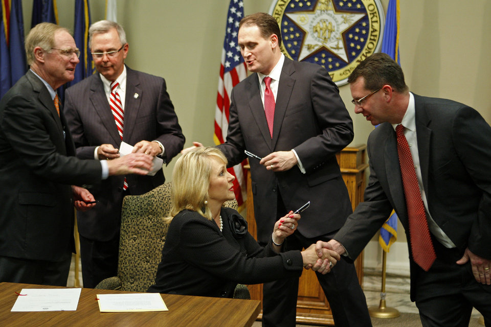 Photo - Gov. Mary Fallin shakes hands Tuesday with  House Speaker Kris Steele, R-Shawnee, in front of Oklahoma State University President Burns Hargis, left, Senate President Pro Tem Brian Bingman, R-Sapulpa, and Rep. Scott Martin, R-Norman, after signing into law an energy efficient measure at the state Capitol.   BRYAN TERRY - THE OKLAHOMAN