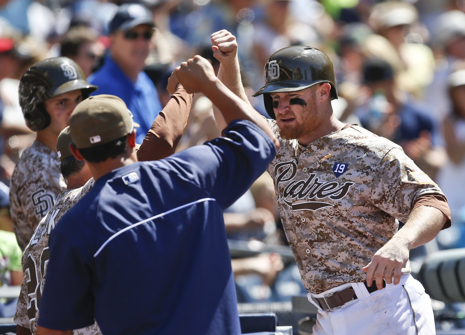 Photo - San Diego Padres' Brooks Conrad is greeted at the dugout after his solo home run against the San Francisco Giants in the seventh inning of a baseball game Sunday, July 6, 2014, in San Diego.  (AP Photo/Lenny Ignelzi)