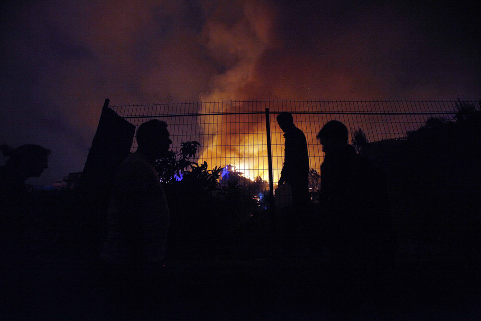 Photo - People watch as a forest fire rages towards urban areas in the city of Valparaiso, Chile, Sunday, April 13, 2014. Authorities say the first fire has destroyed at least 150 homes and is forcing evacuations. ( AP Photo/ Luis Hidalgo)