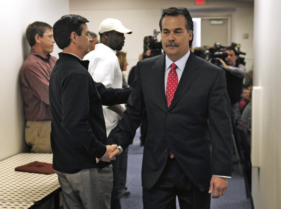 Photo -   Former Tennessee Titans head coach Jeff Fisher, right, shakes hands with Jerry Blessing, community relations coordinator, as Fisher leaves an NFL football news conference at the team's headquarters on Friday, Jan. 28, 2011, in Nashville, Tenn. The Titans announced on Thursday that Fisher will not remain as head coach. (AP Photo/The Tennessean, George Walker IV)