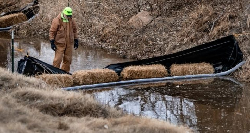 Photo -  City of Oklahoma City Parks and Recreation's Larry Miller checks the drainage ditch barriers used to catch debris as crews work to drain the mile-long Bricktown Canal in Oklahoma City, Okla Tuesday, Jan. 21, 2020. The canal holds 3 million gallons of water, and will take up to two weeks to clean out the silt and debris.   [Chris Landsberger/The Oklahoman]