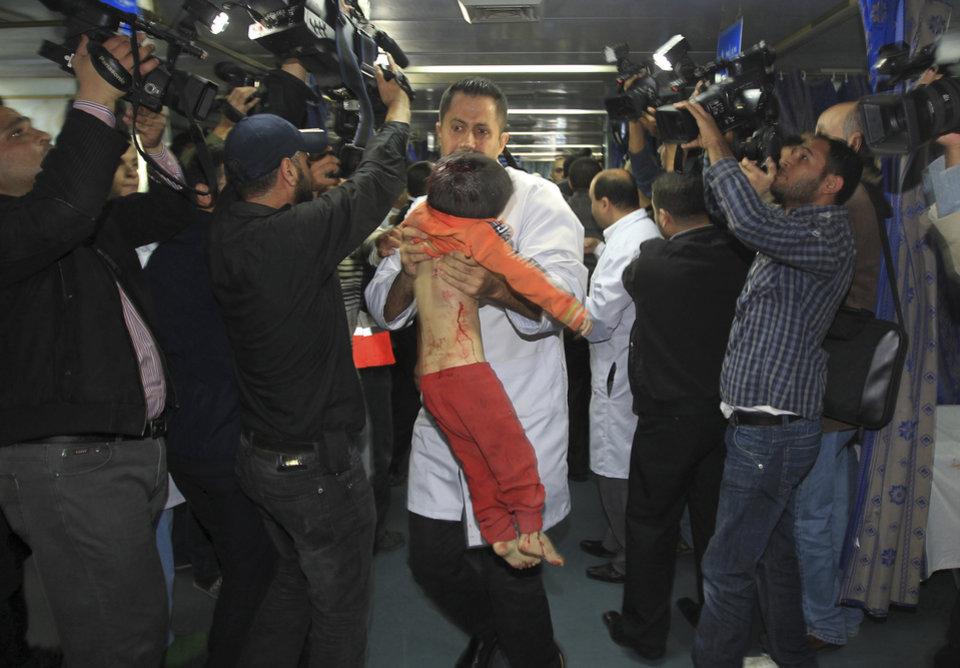 A medic carries the body of a Palestinian boy, who they claim was killed in an Israeli strike on Gaza City, to an event in which media were invited to cover the visit of Hamas Prime Minister Ismail Haniyeh and Egyptian Prime Minister Hesham Kandil at Shifa hospital in Gaza City, Friday, Nov. 16, 2012. Neighbors said the boy was killed in a blast around 8:30 a.m. Friday, around the time Kandil was entering the territory. Israel, which ordinarily confirms strikes, vociferously denied carrying out any form of attack in the area since the previous night. (AP Photo/Mahmud Hams, Pool)