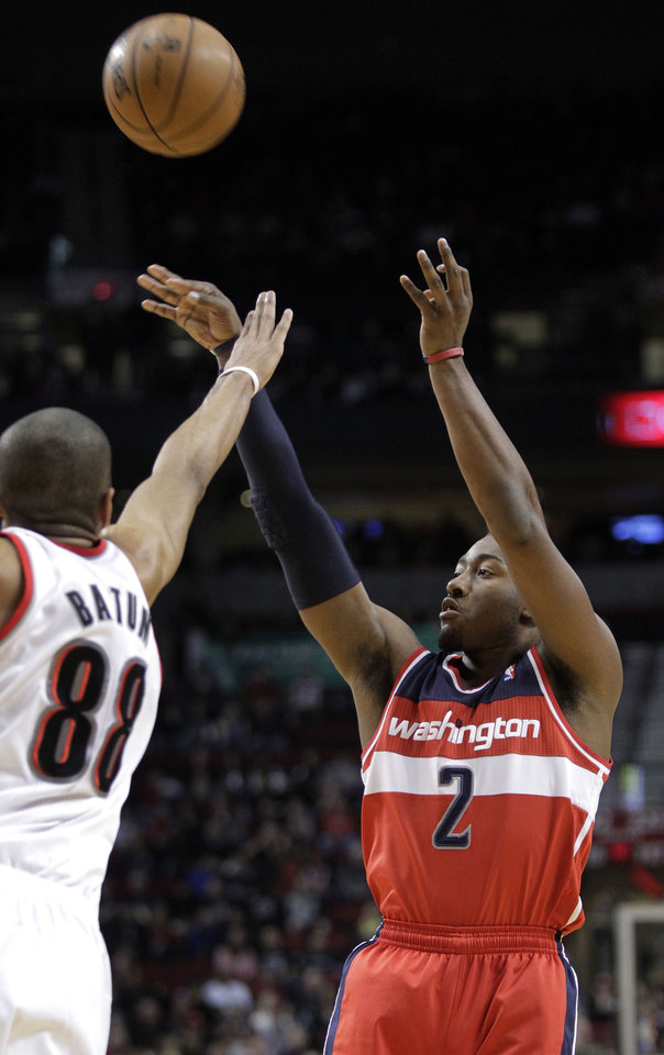 Washington Wizards guard John Wall, right, shoots against Portland Trail Blazers forward Nicolas Batum during the first quarter of an NBA basketball game in Portland, Ore., Monday, Jan. 21, 2013. (AP Photo/Don Ryan)