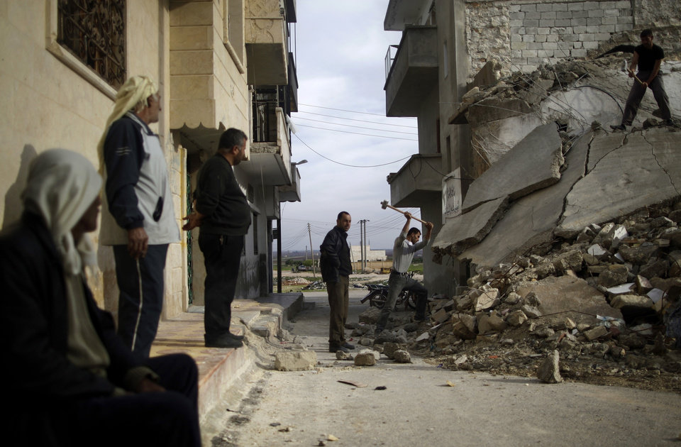 Photo - Syrian men use sledgehammers to break the concrete of a residential building destroyed in a government airstrike, while searching for belongings under the rubble, in Maaret Misreen, near Idlib, Syria, Wednesday, Dec. 12, 2012. (AP Photo/Muhammed Muheisen)