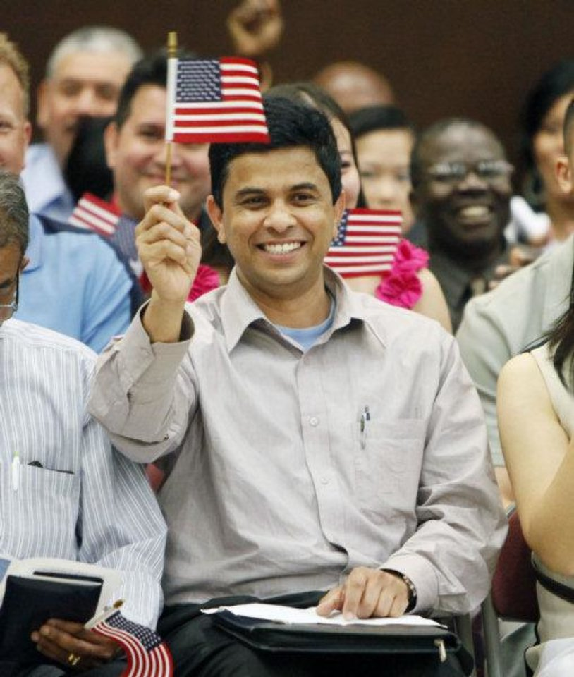Photo - Geoge Varghese, a native of India, expresses his joy at becoming a new U.S. citizen by waving the American flag during a June 24 naturiization ceremony at the federal courthouse in Oklahoma City.  PAUL HELLSTERN - THE OKLAHOMAN