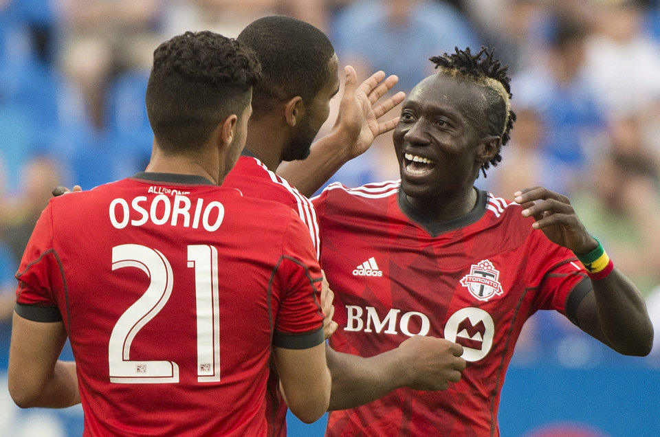 Photo - Toronto FC's Luke Moore, center, celebrates with teammates Jonathan Osorio, left, and Dominic Oduro after scoring against the Montreal Impact during the second half of a soccer match in Montreal, Saturday, Aug. 2, 2014. (AP Photo/The Canadian Press, Graham Hughes)
