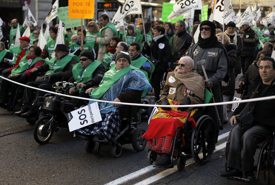 Photo - People march on wheelchairs as they carry  banners reading,