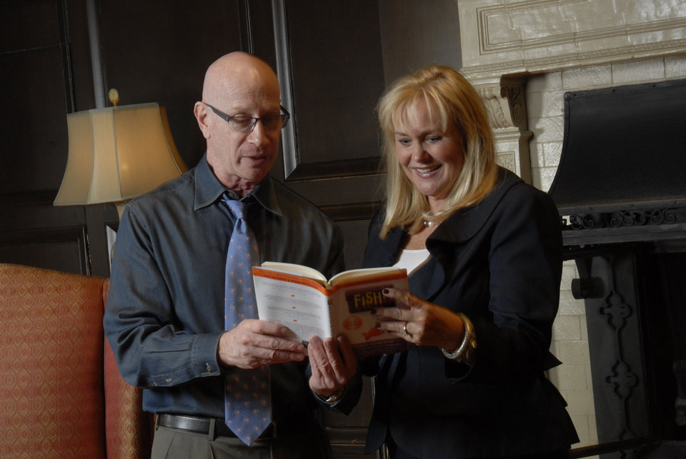 "Author Harry Paul and Susan Zabel, of Express Employment Professionals, look over Paul's ""Fish!"" book. PHOTO PROVIDED"