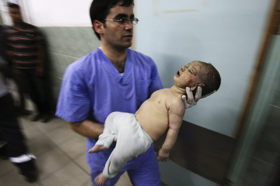 Photo - A medic carries a Palestinian baby injured in Israeli shelling in a hospital in Rafah in the southern Gaza Strip, Friday, Aug. 1, 2014. (AP Photo/Eyad Baba)