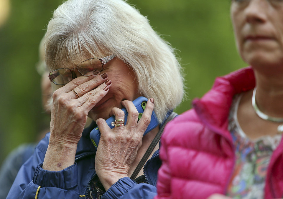 Photo - A woman wipes away tears at the Ground Zero memorial site while watching the dedication ceremony of the National September 11 Memorial Museum at in New York on Thursday, May 15, 2014.  (AP Photo/Spencer Platt, Pool)