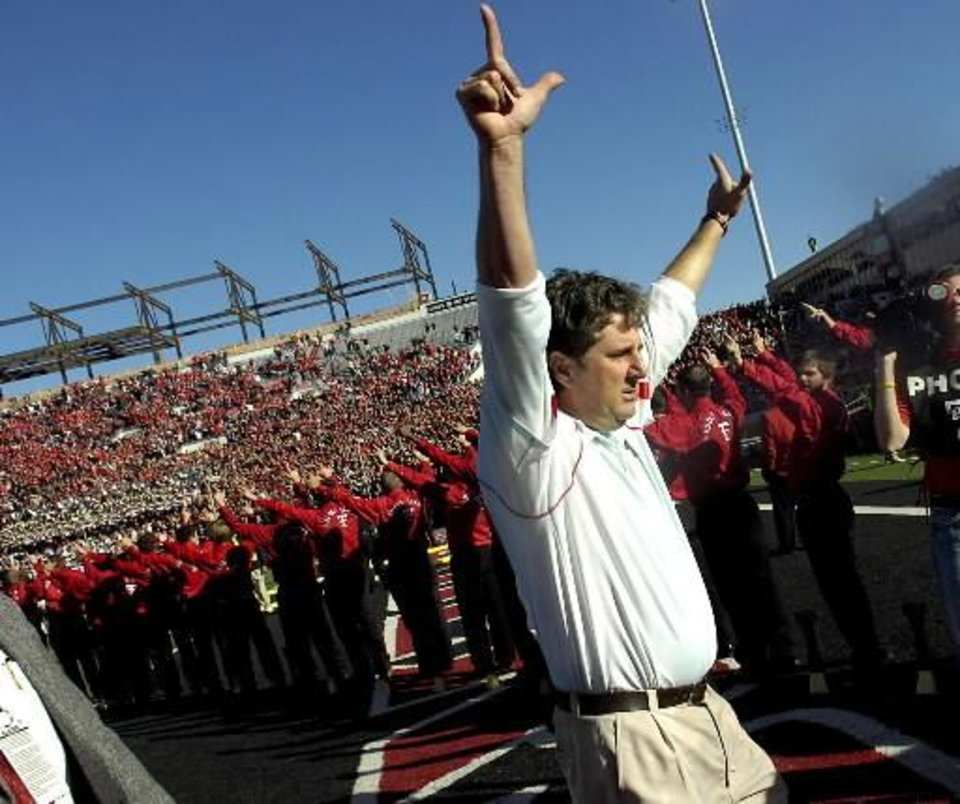 Photo - In this photo taken on Nov. 21, 2009, Texas Tech football coach  Mike  Leach hoists guns up to the crowd as he leaves the field following their 41-13 victory over Oklahoma in an NCAA college footballg ame in Lubbock Texas. The victory earned him the winningest Texas Tech football coach with 83 wins. Texas Tech suspended  Leach on Monday, Dec. 28, while the school investigated complaints from receiver Adam James and his family about how the coach treated the player after a concussion. (AP Photo/Lubbock Avalanche-Journal, Geoffrey McAllister)