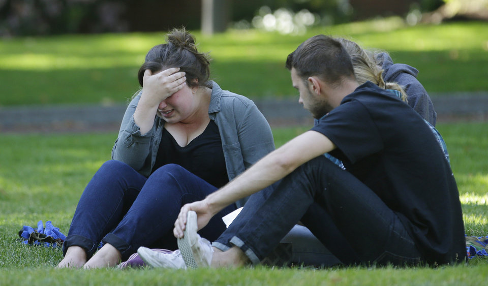 Photo - A woman cries as she sits with others near a prayer circle on the campus of Seattle Pacific University, Friday, June 6, 2014 in Seattle. Classes were cancelled Friday following a shooting at Otto Miller Hall Thursday afternoon.   A 19-year-old man was fatally shot and two other young people were wounded after a gunman entered the foyer  and started shooting.  Aaron R. Ybarra, 26, was booked into the King County Jail late Thursday for investigation of homicide, according to police and the jail roster. (AP Photo/Ted S. Warren)