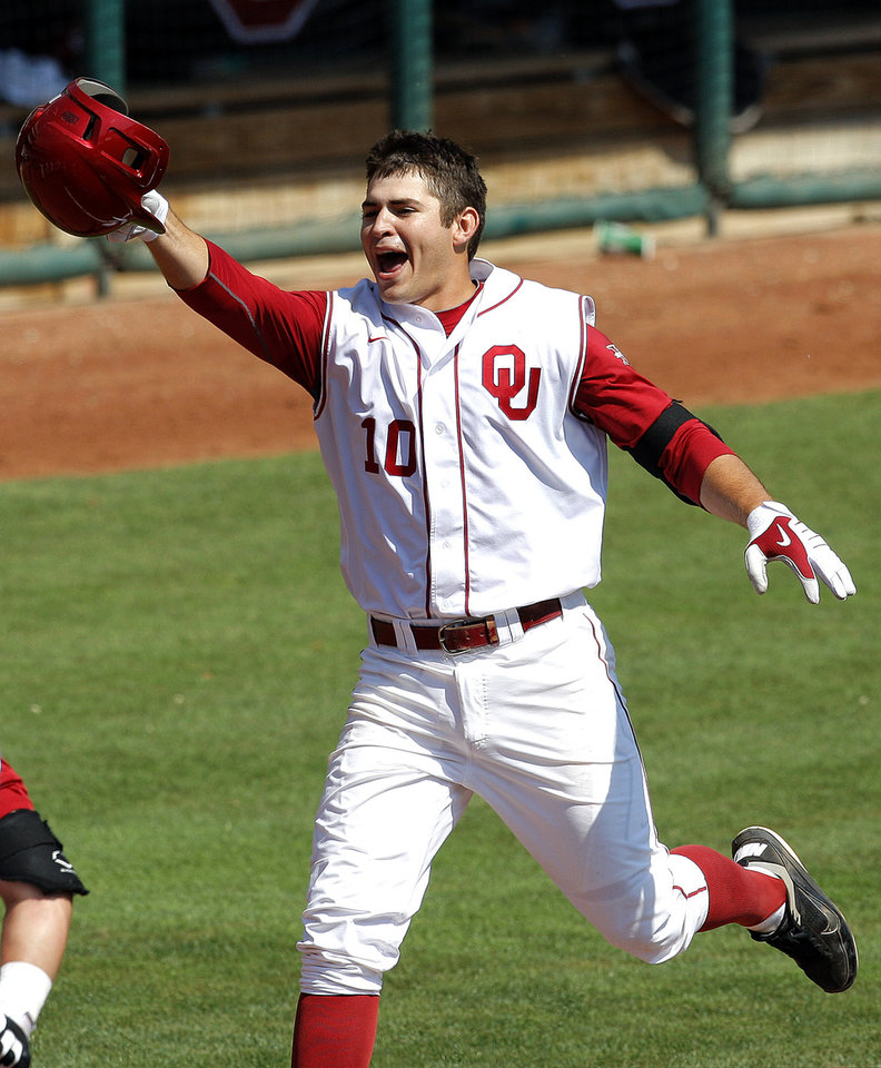 Photo - Oklahoma's Garrett Carey celebrates a walk-off home run during the Big 12 baseball tournament game between Oklahoma State University and the University of Oklahoma at the Chickasaw Bricktown Ballpark in Oklahoma City,  Wednesday, May 23, 2012. Photo by Sarah Phipps, The Oklahoman.