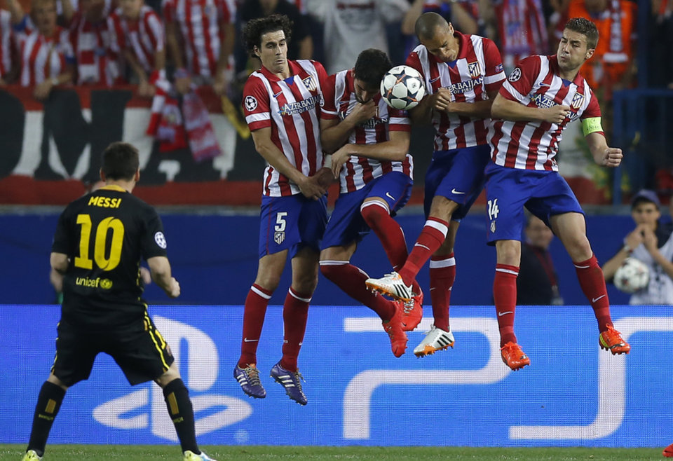Photo - Barcelona's Lionel Messi kicks the ball in front of Atletico players during the Champions League quarterfinal second leg soccer match between Atletico Madrid and FC Barcelona at the Vicente Calderon stadium in Madrid, Spain, Wednesday, April 9, 2014. (AP Photo/Andres Kudacki)