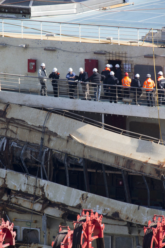 Photo - Captain Francesco Schettino, third from left, talks on the upper deck of the wreck of the Costa Concordia cruise ship, just off the coast of the Giglio island, Thursday, Feb. 27, 2014. The captain of the Costa Concordia has been permitted to go aboard the shipwreck for the first time since it capsized two years ago as part of a new court-ordered search. Consumer groups and lawyers for Capt. Francesco Schettino asked the court in Grosseto to authorize the searches to determine if any factors beyond human error contributed to the disaster. After searching the bridge and elevators last month, experts will examine the emergency generators Thursday. (AP Photo/Andrew Medichini)