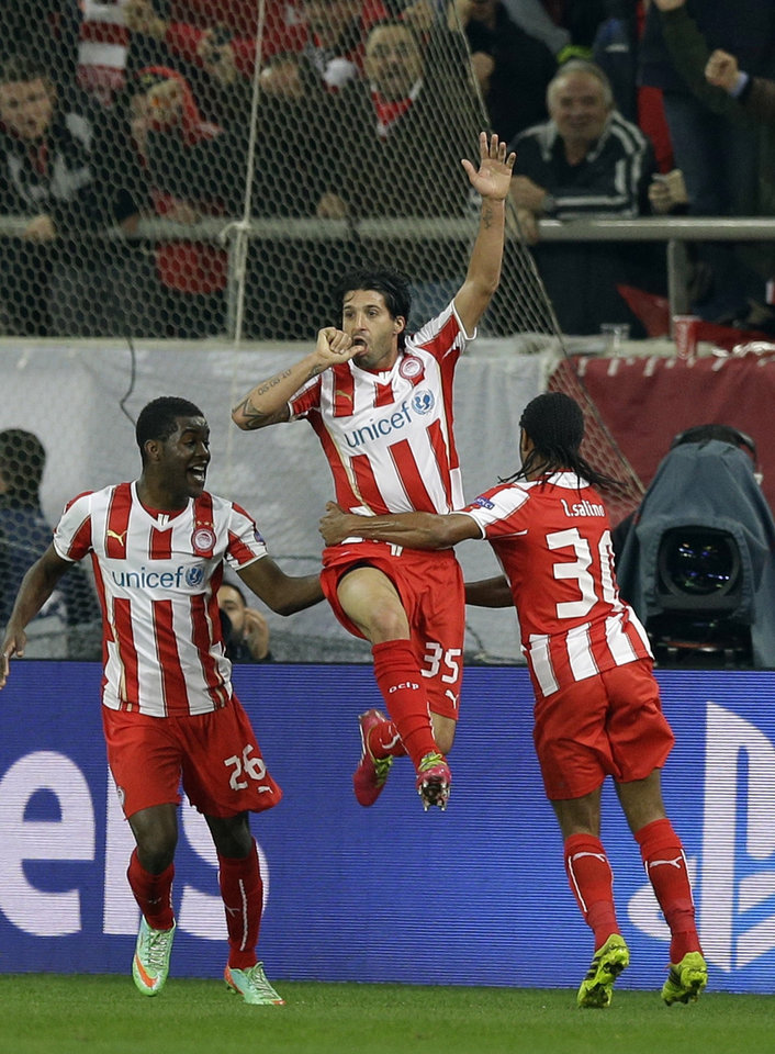 Photo - Olympiakos' Alejandro Dominguez, center, celebrates after scoring the opening goal, during the Champions League, round of 16, first leg soccer match against Manchester United, at Georgios Karaiskakis stadium, in Piraeus port, near Athens, on Tuesday, Feb. 25, 2014. (AP Photo/Thanassis Stavrakis)