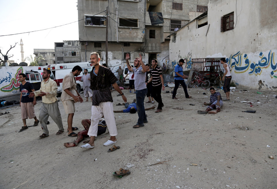 Photo - Palestinians help others laying on the ground following an Israeli Strike in Shijaiyah neighborhood, eastern Gaza City, Wednesday, July 30, 2014. (AP Photo/Adel Hana)